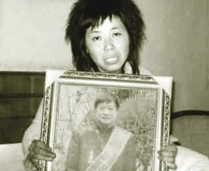 死者妻子曾静芳捧着丈夫魏文华的生前照片